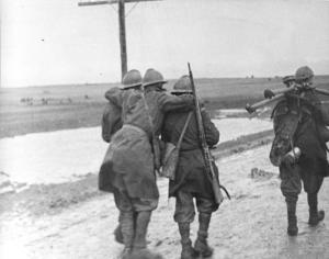 Avance inicial. La infantería italiana en la meseta de Trijueque. Dos soldados ayudan a un herido; un tercer soldado transporta un trípode de ametralladora. Fuente: Bundesarchiv