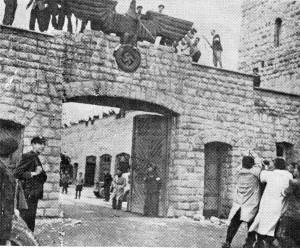 Españoles (abajo con gabardinas) derriban el águila en la puerta del campo de concentración de Mauthausen.